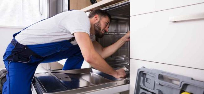 appliance repair technician working on a dishwasher