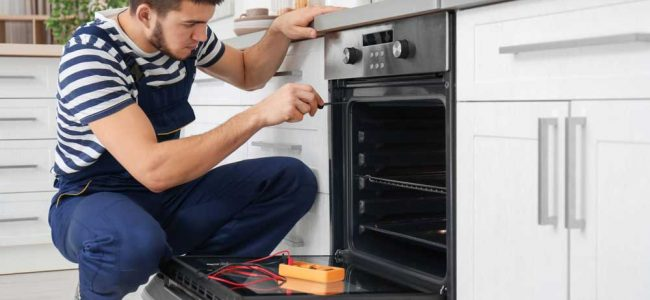 appliance repair technician working on an oven